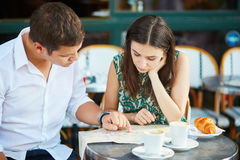 Jeunes ajouter romantiques à la carte en café français Photos stock