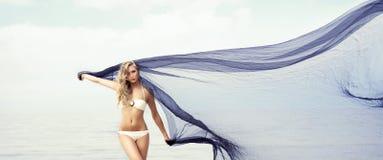 Jeunes, ajustement et belle femme sur la danse de plage avec un blowi photographie stock libre de droits