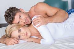 Jeunes amants doux se trouvant sur le lit regardant la came image stock