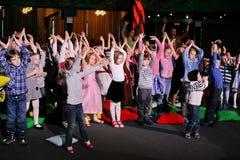 Jeunes amateurs de théâtre enfants observant avec enthousiasme le théâtre Smeshariki de spectacle de marionnettes de Noël des enf Photographie stock