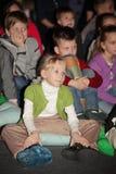Jeunes amateurs de théâtre enfants observant avec enthousiasme le théâtre Smeshariki de spectacle de marionnettes de Noël des enf Photo stock