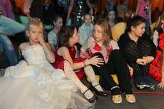 Jeunes amateurs de théâtre enfants observant avec enthousiasme le théâtre Smeshariki de spectacle de marionnettes de Noël des enf Photo libre de droits