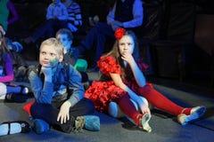 Jeunes amateurs de théâtre enfants observant avec enthousiasme le théâtre Smeshariki de spectacle de marionnettes de Noël des enf Image libre de droits