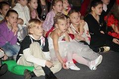 Jeunes amateurs de théâtre enfants observant avec enthousiasme le théâtre Smeshariki de spectacle de marionnettes de Noël des enf Image stock