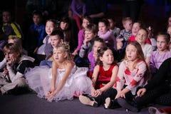 Jeunes amateurs de théâtre enfants observant avec enthousiasme le théâtre Smeshariki de spectacle de marionnettes de Noël des enf Photos stock