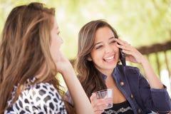 Jeunes amies adultes expressives parlant au téléphone intelligent Photos stock
