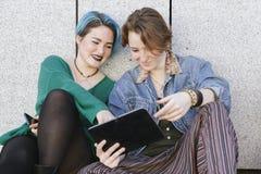 Jeunes amies avec le mode de vie de diversité utilisant la technologie et Image stock