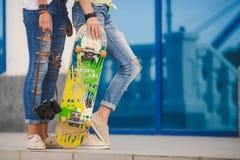 Jeunes amies ayant l'amusement avec une planche à roulettes Images stock