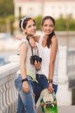 Jeunes amies ayant l'amusement avec une planche à roulettes Photos libres de droits