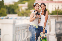 Jeunes amies ayant l'amusement avec une planche à roulettes Image libre de droits