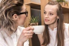 Jeunes amies buvant du café et se souriant Photo stock