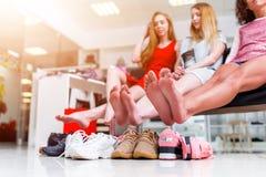Jeunes amies de sourire s'asseyant dans un magasin d'habillement regardant leurs pieds nus et pile de nouvelles chaussures et de  Image libre de droits