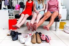 Jeunes amies de sourire s'asseyant dans un magasin d'habillement regardant leurs pieds nus et pile de nouvelles chaussures et de  Photographie stock
