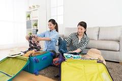 Jeunes amies emballant des vêtements mis dans la valise Image libre de droits