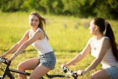 Jeunes amies faisant un cycle au soleil Image stock