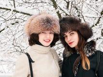 Jeunes amies heureuses adorables de femmes de brune dans des chapeaux de fourrure ayant la forêt neigeuse de parc d'hiver d'amuse Photos libres de droits