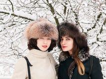 Jeunes amies heureuses adorables de femmes de brune dans des chapeaux de fourrure ayant la forêt neigeuse de parc d'hiver d'amuse Photos stock