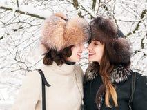 Jeunes amies heureuses adorables de femmes de brune dans des chapeaux de fourrure ayant la forêt neigeuse de parc d'hiver d'amuse Images libres de droits