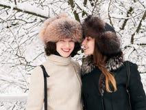 Jeunes amies heureuses adorables de femmes de brune dans des chapeaux de fourrure ayant la forêt neigeuse de parc d'hiver d'amuse Photo libre de droits