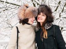 Jeunes amies heureuses adorables de femmes de brune dans des chapeaux de fourrure ayant la forêt neigeuse de parc d'hiver d'amuse Photographie stock libre de droits