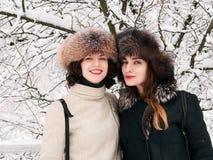 Jeunes amies heureuses adorables de femmes de brune dans des chapeaux de fourrure ayant la forêt neigeuse de parc d'hiver d'amuse Photo stock