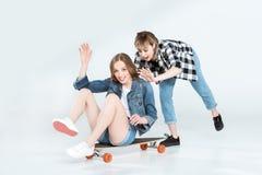 Jeunes amies heureuses attirantes ayant l'amusement avec la planche à roulettes Photographie stock