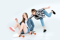 Jeunes amies heureuses ayant l'amusement avec la planche à roulettes d'isolement sur le gris Photo libre de droits