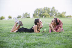 Jeunes amies jouant avec des bulles sur le parc Image libre de droits