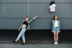 Jeunes amies posant avec le groupe de ballons dehors Photographie stock libre de droits