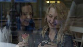 Jeunes amies s'asseyant au bar causant et à l'aide du smartphone vérifiant le media social et jouant des jeux clips vidéos
