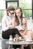 Jeunes amies s'asseyant ensemble et tenant des mains tout en buvant du café Image libre de droits