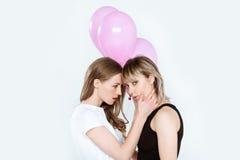 Jeunes amies sensuelles posant ensemble et jugeant des ballons d'isolement sur le gris Photo libre de droits