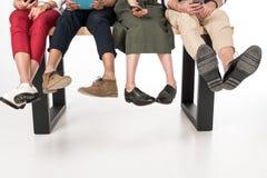 Jeunes amis à l'aide des dispositifs numériques tout en se reposant ensemble sur le banc Photographie stock