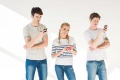Jeunes amis à l'aide des smartphones Photos libres de droits