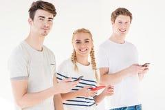 Jeunes amis à l'aide des smartphones Image stock