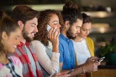 Jeunes amis à l'aide des téléphones portables Image libre de droits