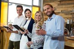 Jeunes amis à l'aide du comprimé numérique et du téléphone portable tout en ayant le café Photo stock