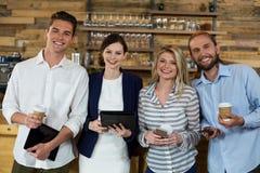 Jeunes amis à l'aide du comprimé numérique et du téléphone portable tout en ayant le café Photos stock