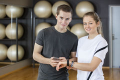Jeunes amis à l'aide du téléphone et du podomètre intelligents dans le gymnase Image stock