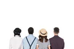Jeunes amis élégants s'asseyant ensemble d'isolement sur le blanc Photo stock