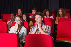 Jeunes amis étonnés observant un film Image stock