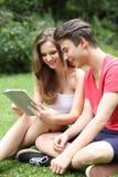 Jeunes amis adolescents partageant un Tablette-PC Image stock