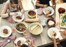 Jeunes amis affamés rempliant dans des spaghetti Images stock