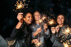 Jeunes amis appréciant avec des cierges magiques Photo stock