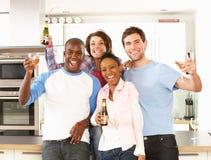 Jeunes amis appréciant la boisson dans la cuisine Photographie stock
