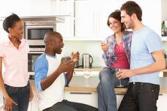 Jeunes amis appréciant la glace de vin dans la cuisine Photos stock
