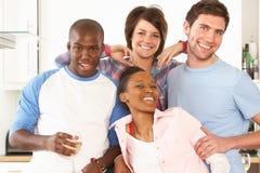 Jeunes amis appréciant la glace de vin dans la cuisine Photos libres de droits
