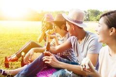 Jeunes amis appréciant le pique-nique et la consommation Image libre de droits