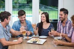 Jeunes amis appréciant le vin et des sushi à la table Photographie stock