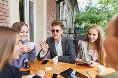 Jeunes amis attirants détendant au café sur un fond brouillé téléphone noir de récepteur de concept de transmission Image stock